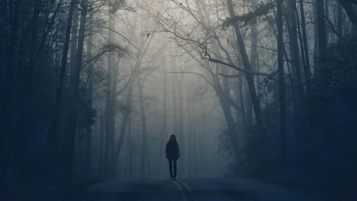 persona che cammina su un sentiero buio