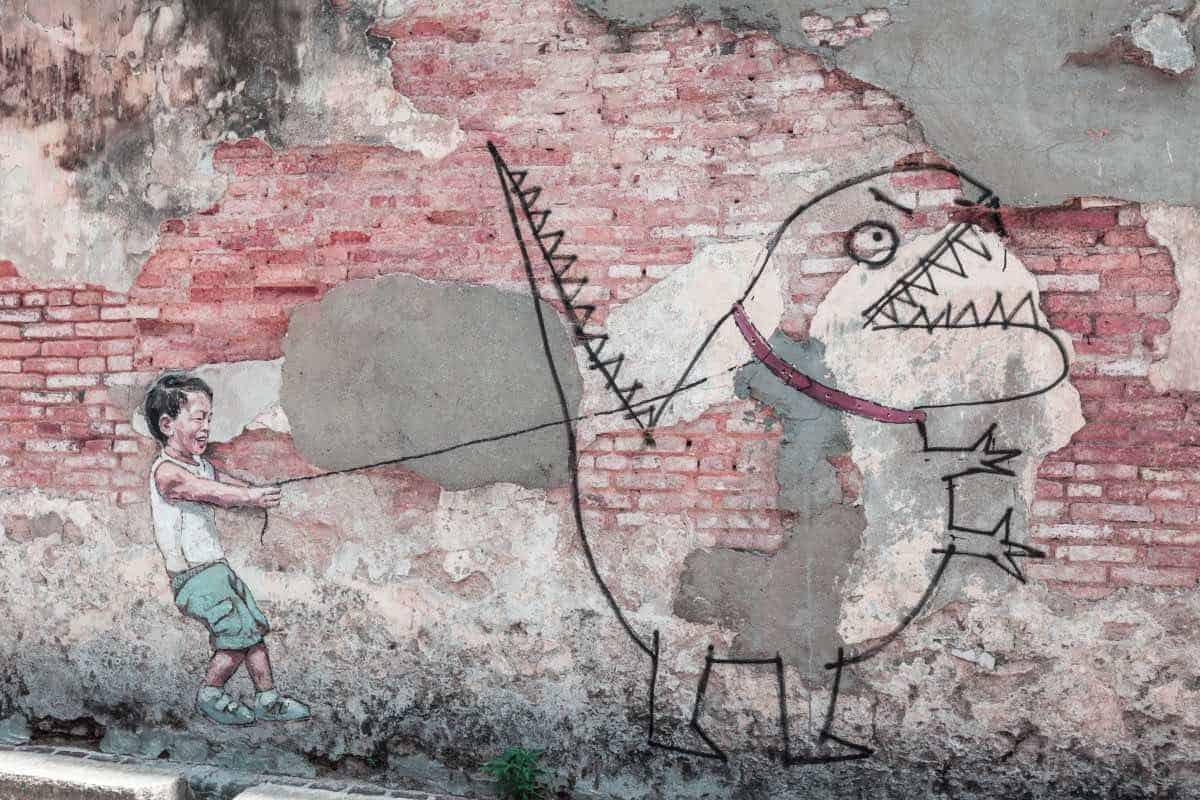 graffito di un bambito che tieni un dinosauro al guinzaglio