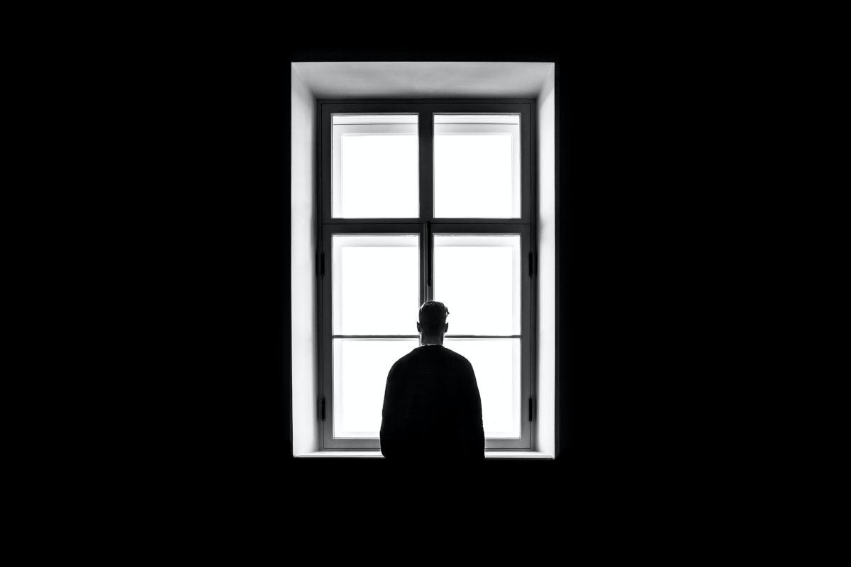 persona che guarda fuori dalla finestra sfondo nero