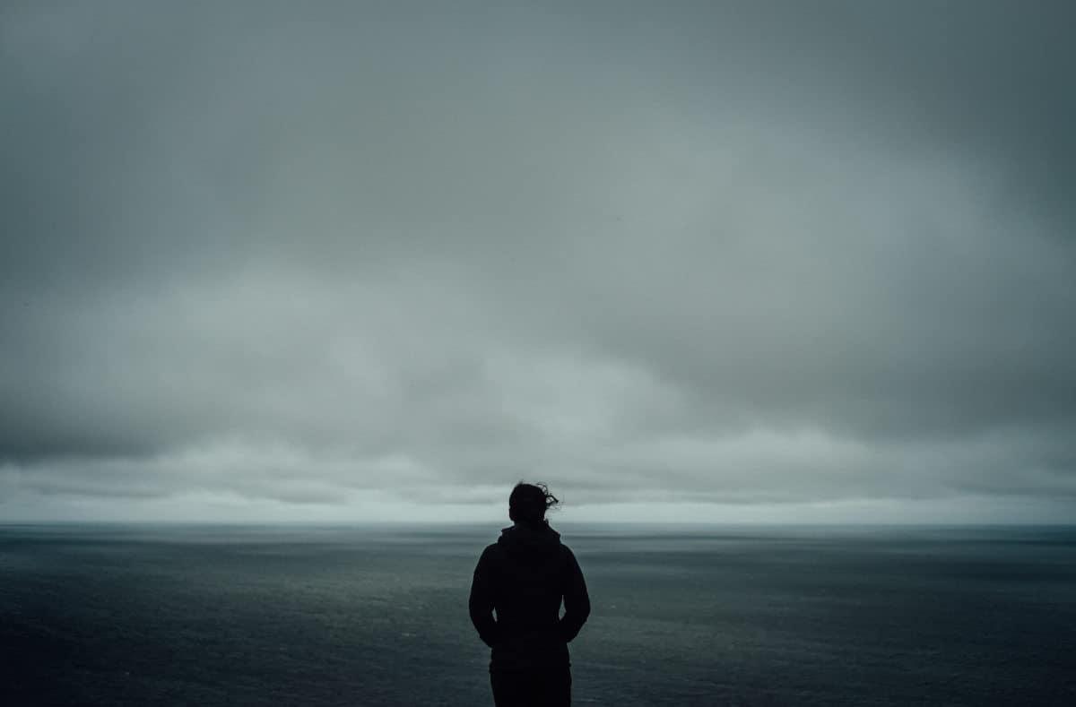 donna che guarda cielo nuvoloso senso di solitudine