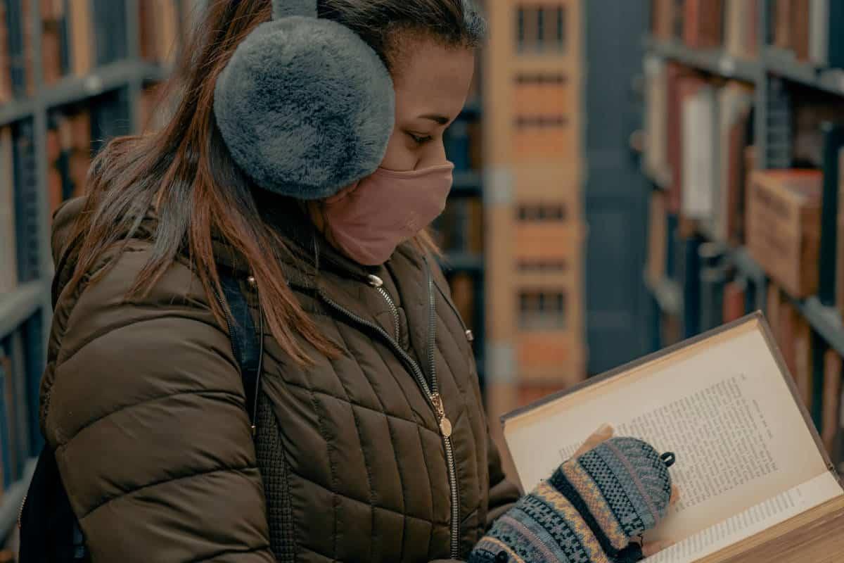 persona in biblioteca con mascherina che legge libro
