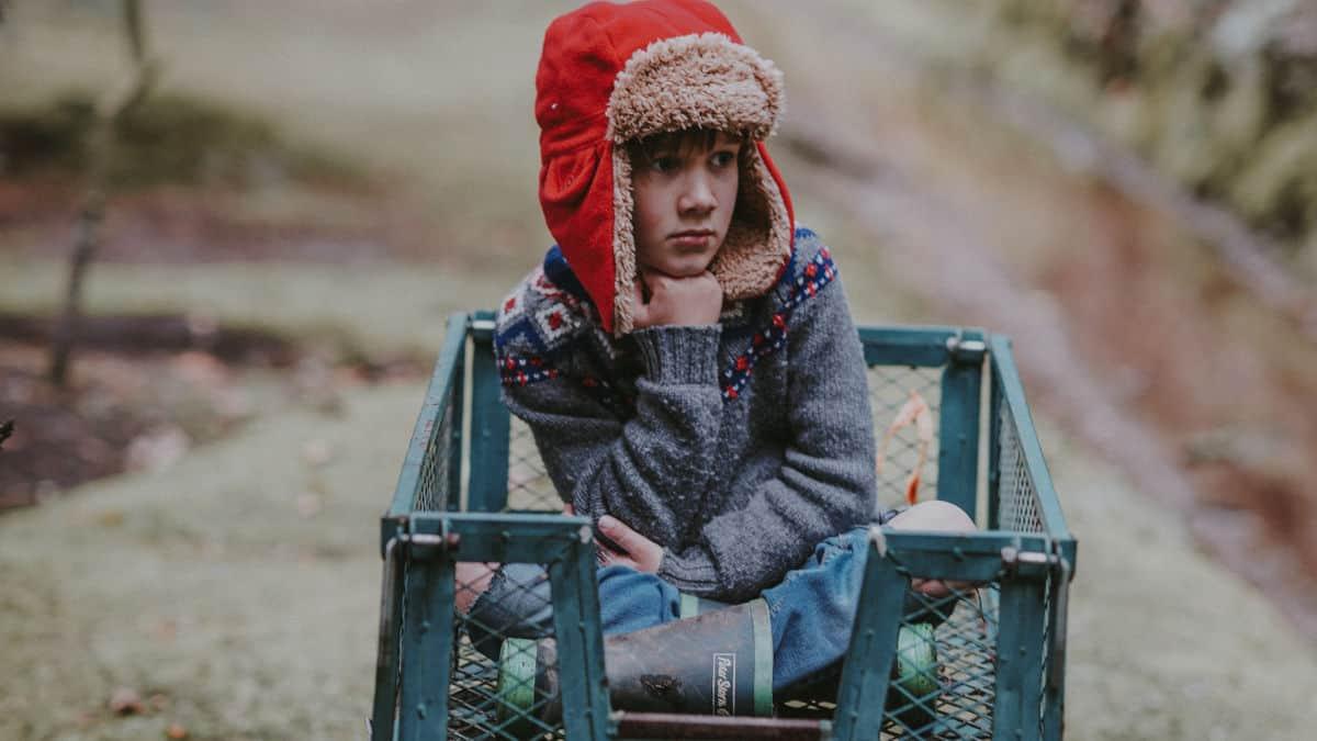 bambino su un carretto in giardino annoiato
