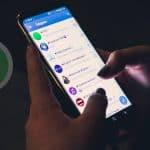 persona che sta guardando le chat su Telegram stanza buia icona WhatsApp in dissolvenza