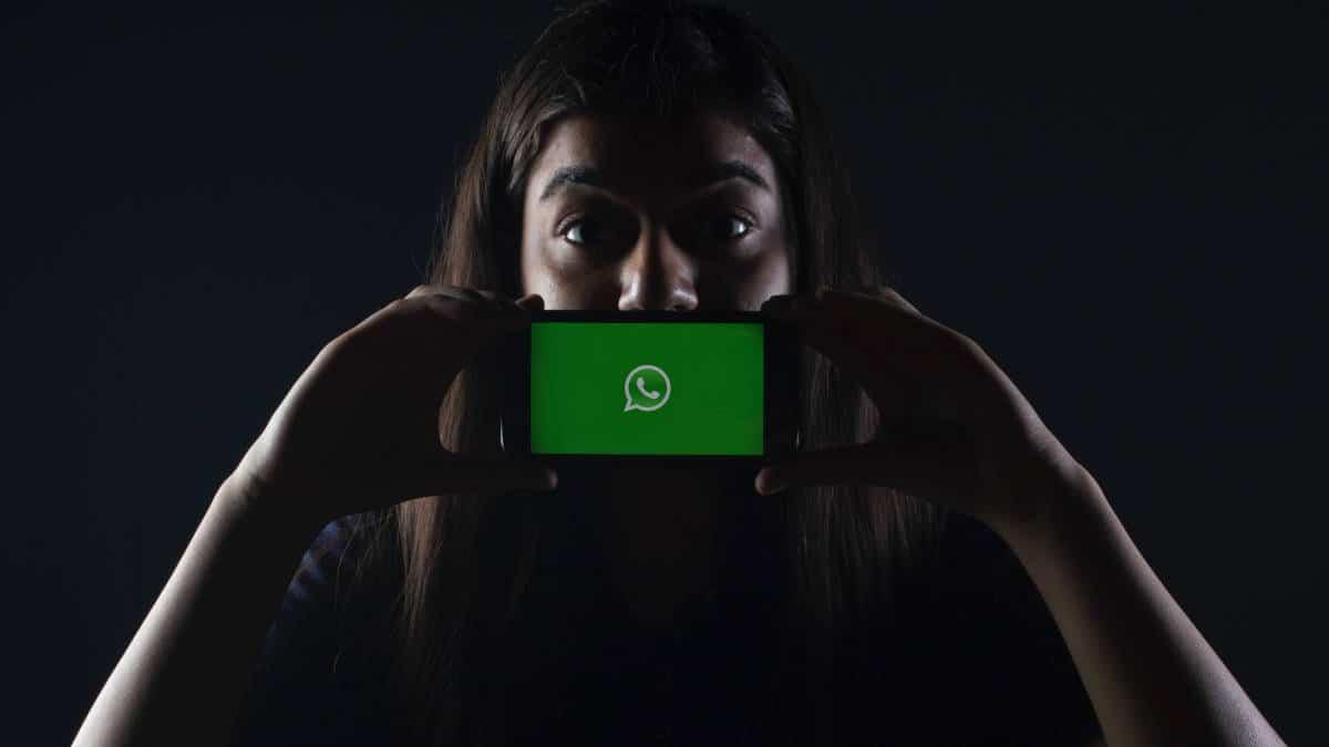 ragazza che esprime stupore con cellulare e schermata WhatsApp