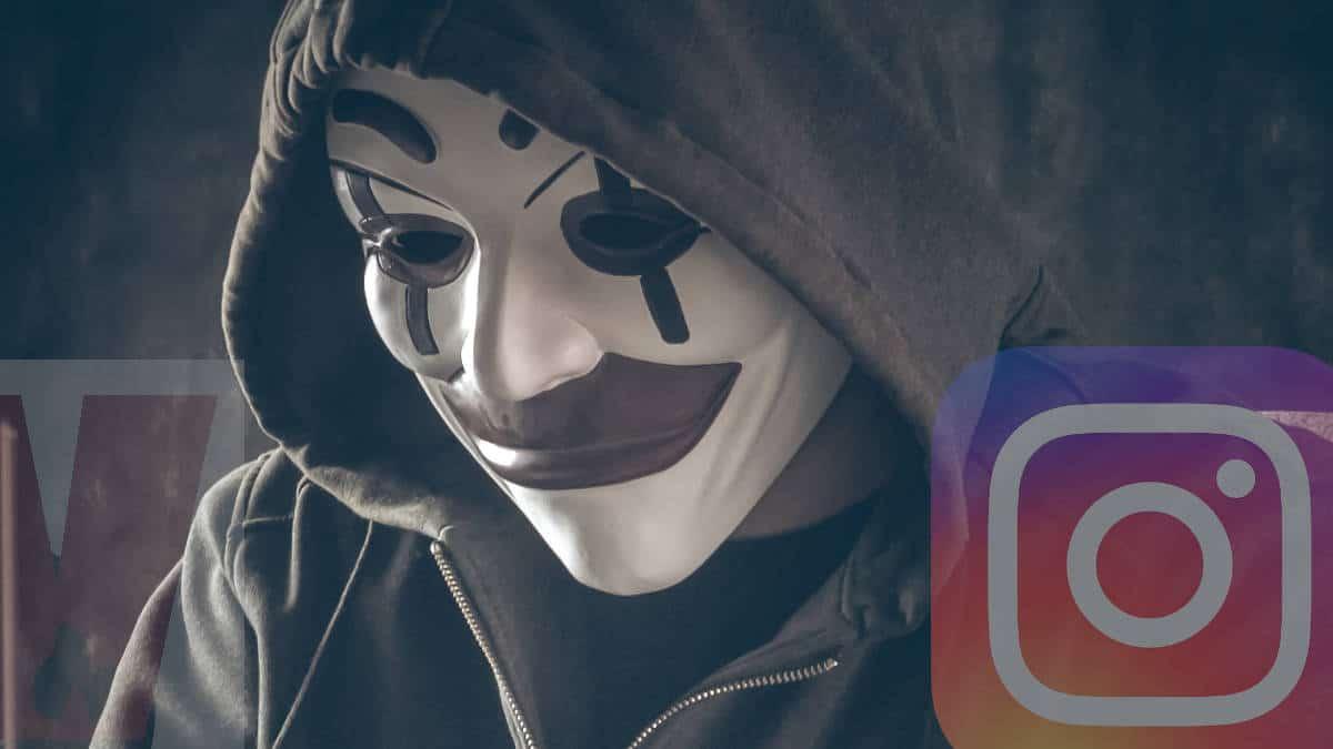 uomo con cappuccio e maschera davanti PC phishing Instagram