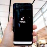 mano con smartphone che apre app TikTok mi piace